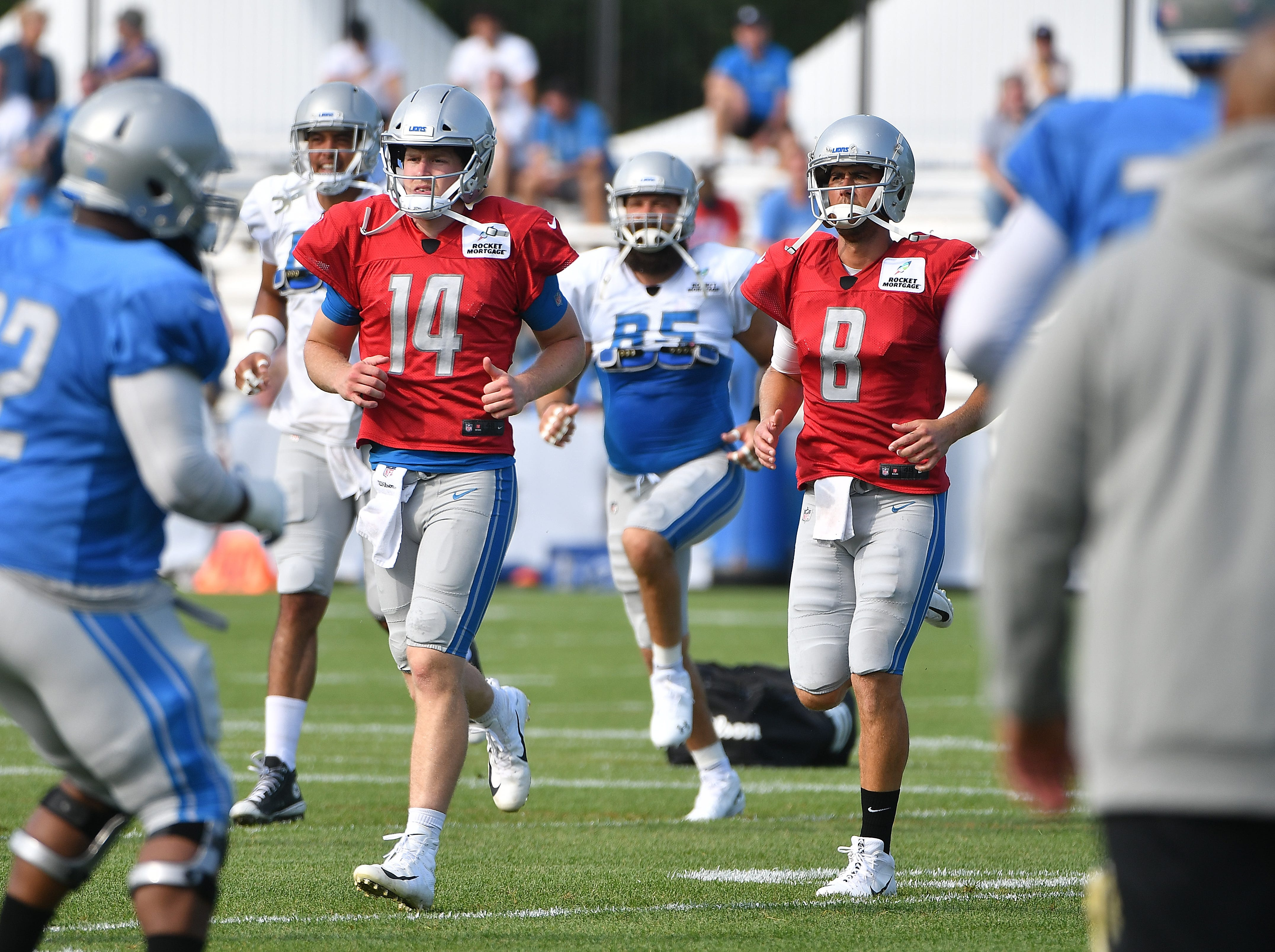 Lions quarterbacks Jake Rudock and Matt Cassel warm up on the field at the start of practice.