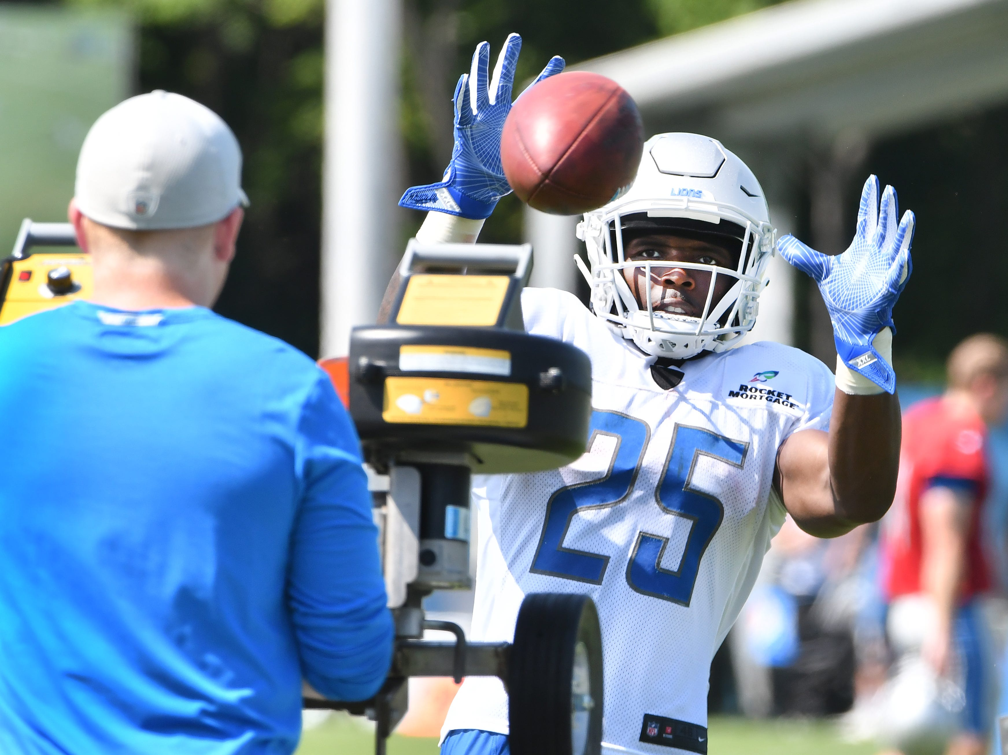 Lions running back Theo Riddick gets up close and personal with the passing machine, taking hard passes just a few feet from the machine at the end of practice.