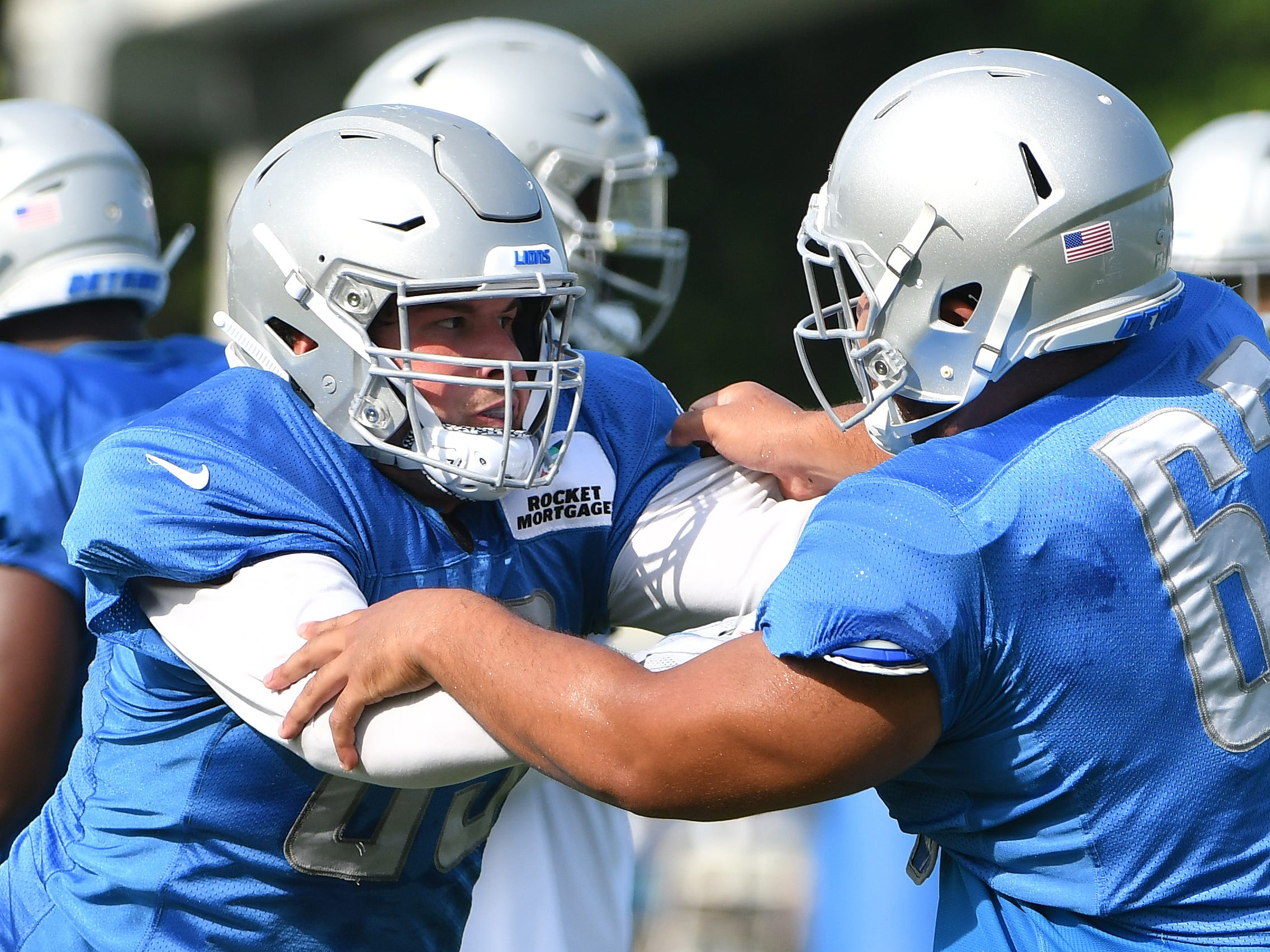Lions defensive end Anthony Zettel and defensive tackle Josh Fatu work during drills.