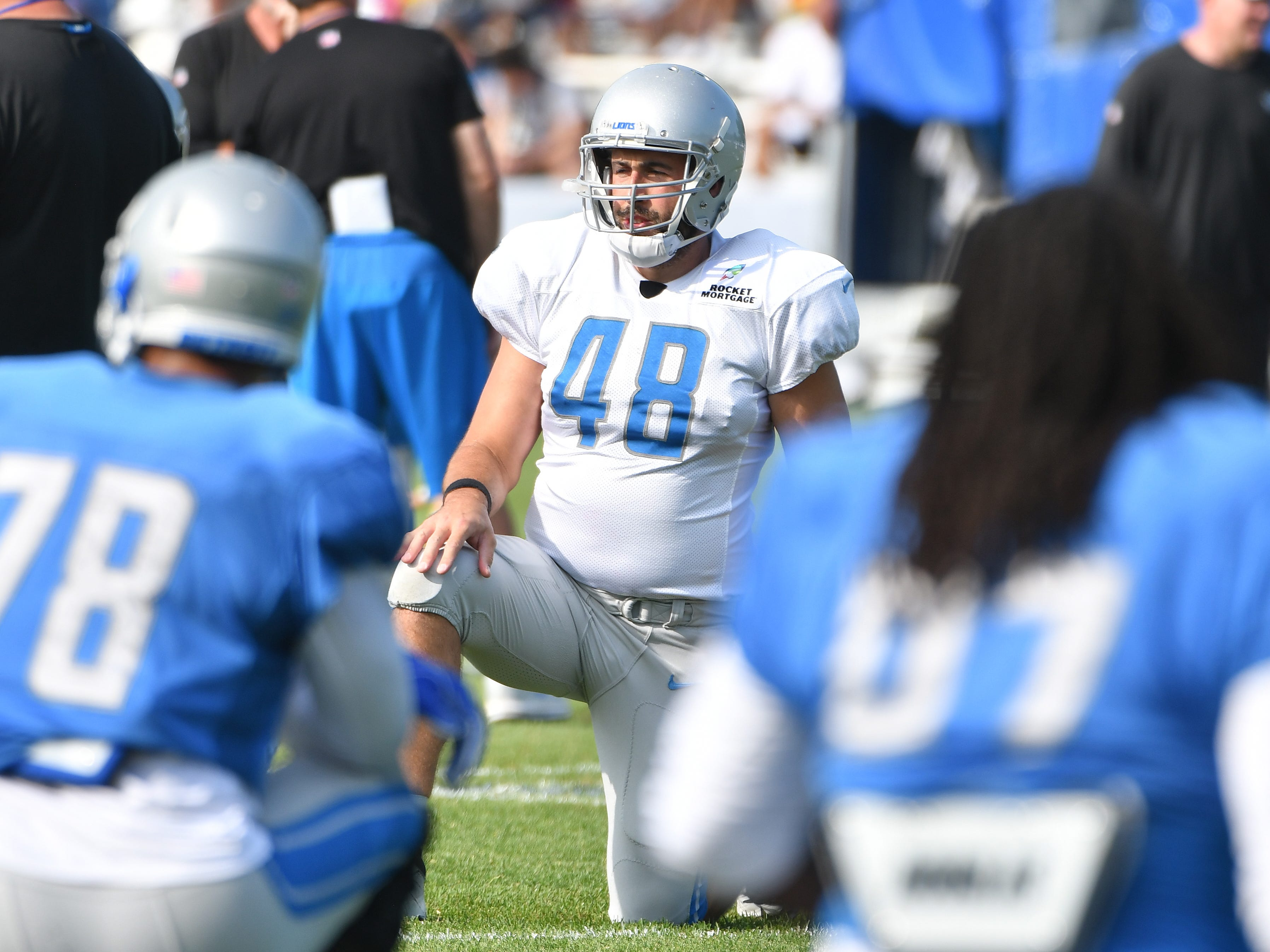 Lions long snapper Don Muhlbach stretches out at the start of practice.