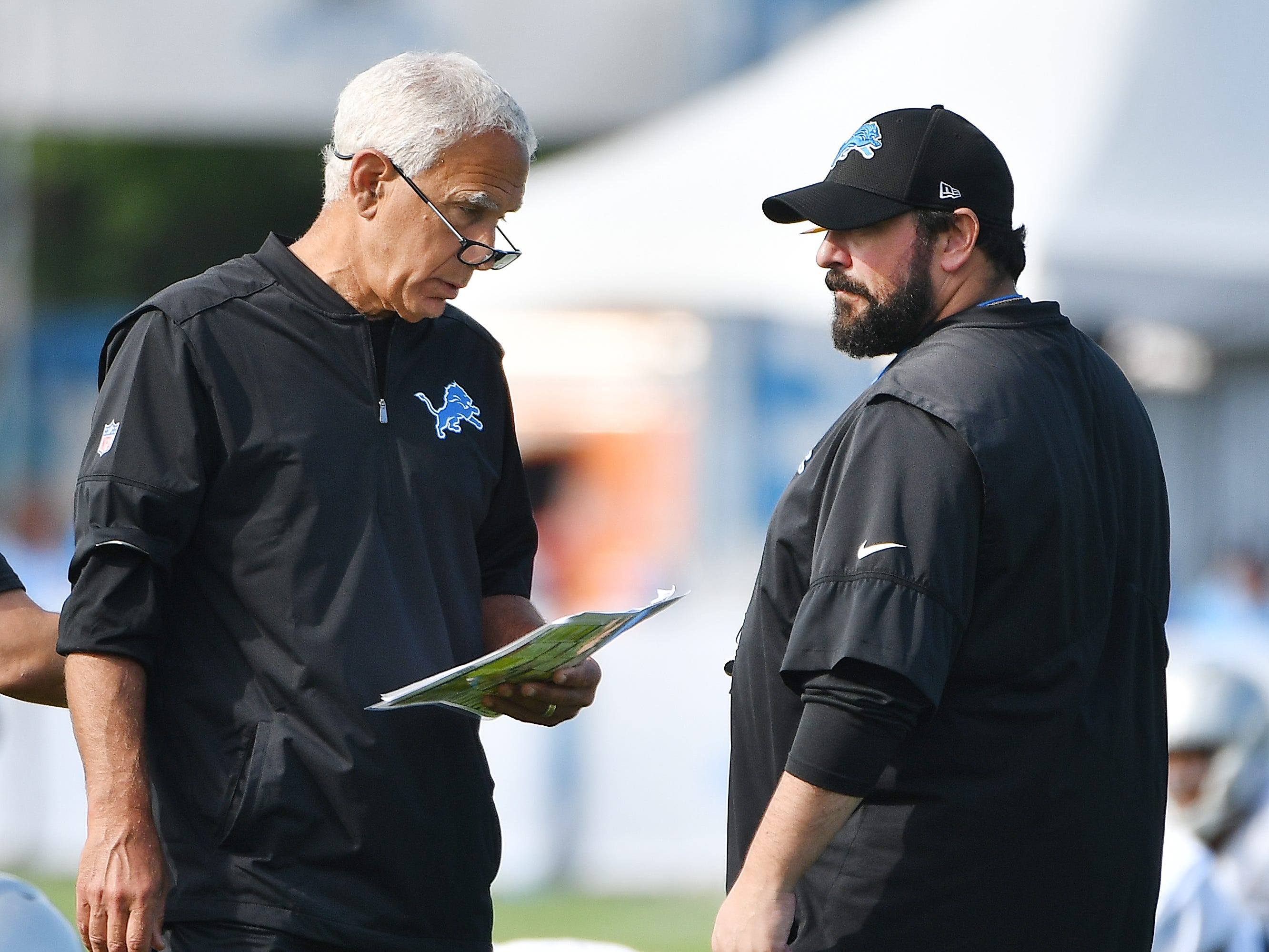 Lions defensive coordinator Paul Pasqualoni and head coach Matt Patricia talk on the field during stretching.