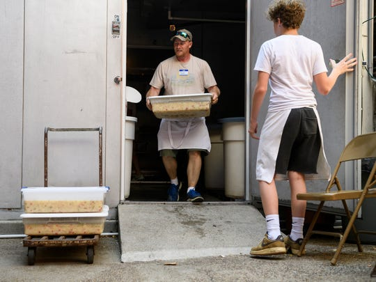 Volunteers Scott Tieken and Erich Bockstege, not pictured, load up a cart of plastic containers filled with German potato salad to deliver to the Germania Maennerchor outdoor food booths on Volksfest's opening day, Thursday, Aug. 2, 2018.