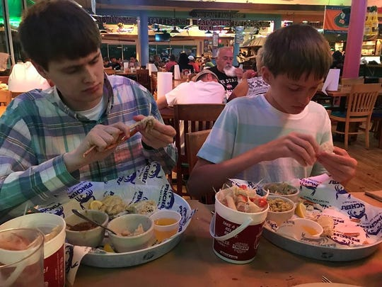 Angela Seldal, a native of Illinois, traveled with her family to Fort Myers Beach for a 9-day trip, not knowing the beach was in bad condition. Her sons, Mak and Aiden, sit inside at Pinchers after the family reconsidered eating outside at a beachfront restaurant.