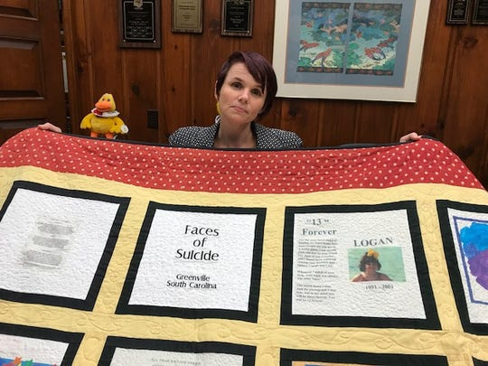 Susan Haire with Faces of Suicide quilt