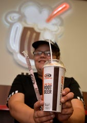 Desiree Walker holds up a root beer float on Wednesday afternoon at the A&W All American Food restaurant on Central Avenue.  Monday, August 6th from 2-8 p.m., A&W will be handing out free root beer floats for national root beer float day and is encouraging patrons to donate Disabled American Veterans.