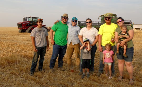 Bridger Zeigler, Ben Goss, Eli Legan, Cassie Bahnmiller, Kallan Bahnmiller, Keely Bahnmiller, Colton, 5,  Charlotte, 3, and Sam, 1, take a short break for dinner during harvest.