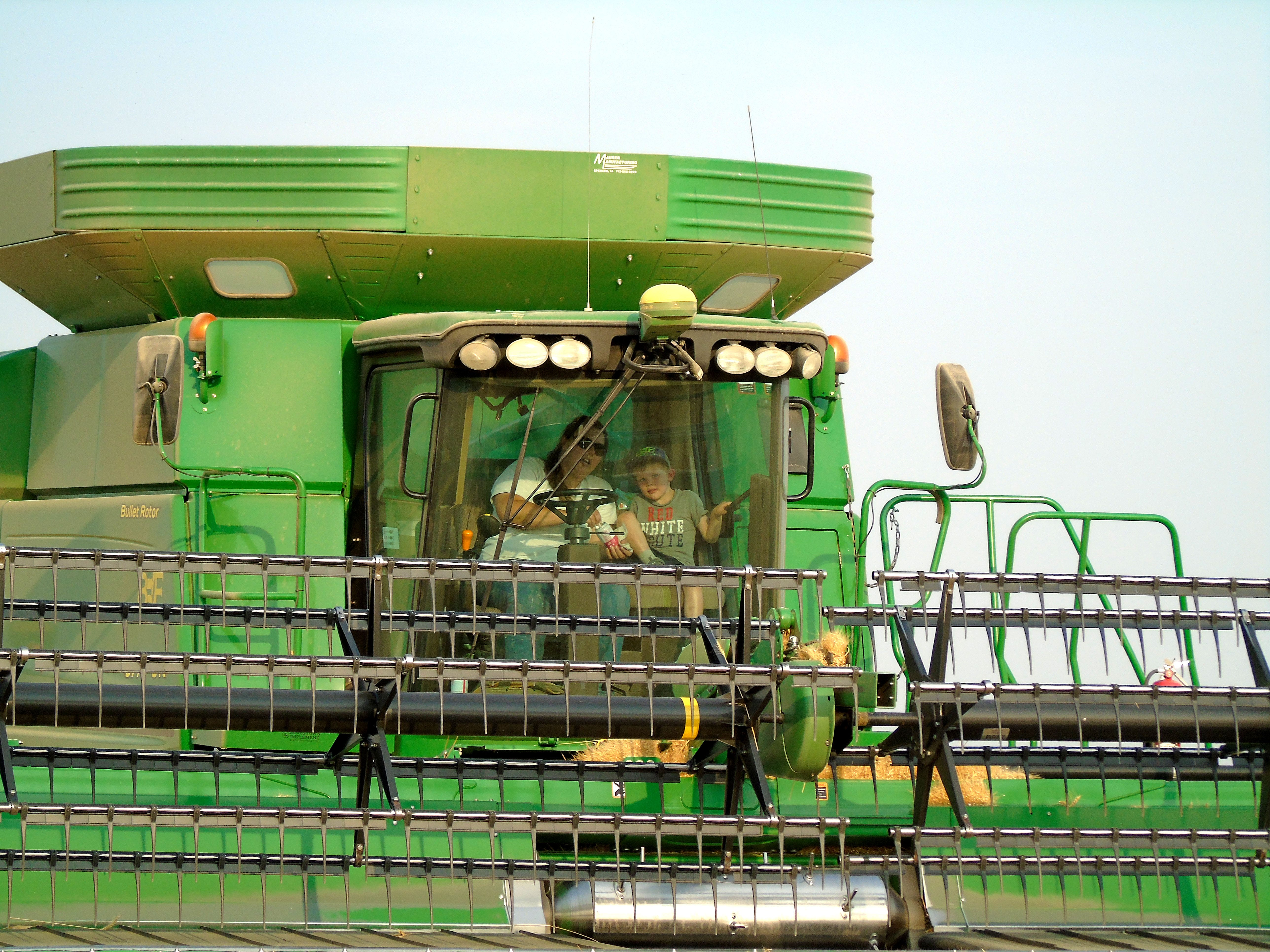 Cassie Bahnmiller and her nephew Colton, 5, harvest winter wheat on the Bahnmiller Family Farms near Big Sandy.