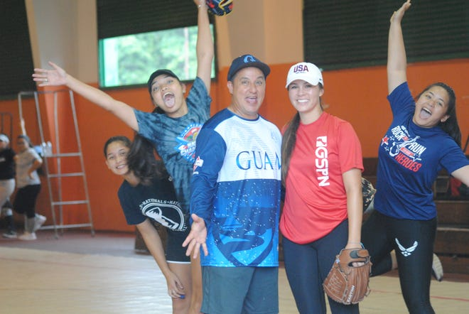 "Madilyn ""Bubba"" Nickles, stops for a photo with Guam baseball and softball legend Keith Hattig. She is being photo-bombed by some of the girls who attended her softball clinic at the Agana Heights gym on Aug. 2."