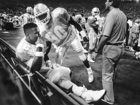 Tennessee quarterback Sterling Henton is comforted by Anthony Morgan after Henton was injured in the second quarter against Colorado State in September 1989.