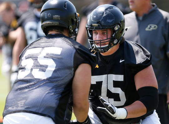 Offensive linemen Shane Evans, right, and Michael Mendez work on blocking drills during football practice Thursday, August 2, 2018, at Purdue.