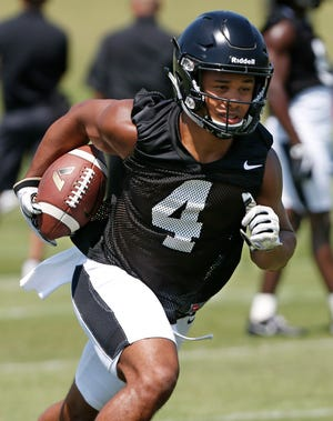 Wide receiver Rondale Moore runs after catching a pass during football practice Thursday.