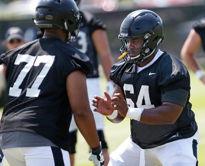 Offensive linemen Dennis Edwards, right, and DJ Washington work on blocking drills during football practice Thursday, August 2, 2018, at Purdue.