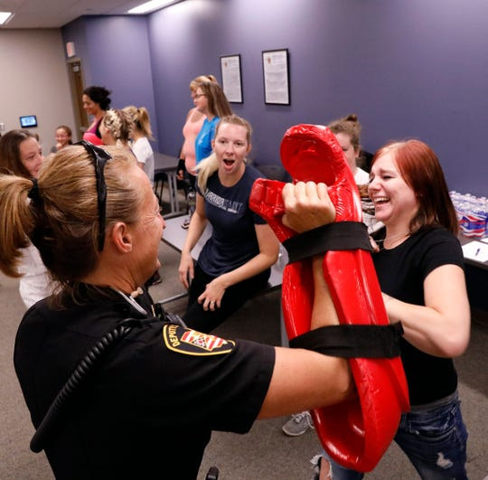 Kelsey Meyers, center, cheers on Karrolle Dusek, right, as she blocks blows from Fairfield County Sheriff's Dep. Tiffany McNabb Friday, July 27, 2018, during a self defense class at the Fairfield County Sheriff's Office in Lancaster. Meyers is an intensive supervision officer with the Fairfield County Common Pleas Court Adult Community Control Department. Dusek is a on community control. The class was for women who are on community control, female community control officers and other court staff. It was part of a voluntary program created by female community control officers to help empower women under the department's supervision.