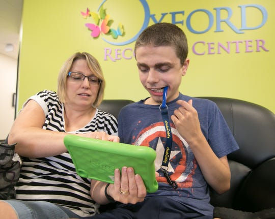 Cindy Zromkoski works with her son Trevor, 15, on a tablet in the lobby of the Oxford Recovery Center Wednesday, Aug. 1, 2018. The Zromkoskis visit the center from Valparaiso, Ind. for Trevor's treatment.