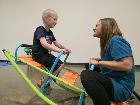 Ayden Spaulding, 7, and behavior assistant Tarin Gurunian take a break from his therapy for a bit of fun at the Oxford Recovery Center Wednesday, Aug. 1, 2018.