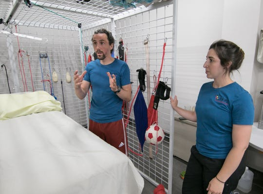 Nico Pisanti, director of suit therapy, explains the process of treating a patient with a special suit while physical therapist Andrea Walker listens at the Oxford Recovery Center in Brighton Wednesday, Aug. 1, 2018.