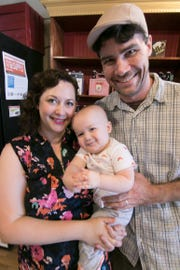 Carly and David Leisk hold their 13-month-old son Milo Thursday, Aug. 2, 2018 inside the building that will become Culture Beer & Cheese in downtown Brighton.
