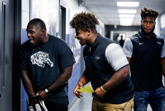 University of Memphis defensive linemen Joseph Dorceus (left) and O'Bryan Goodson (middle) enjoy themselves as they watch teammates during football media day at the team facility on the South Campus.