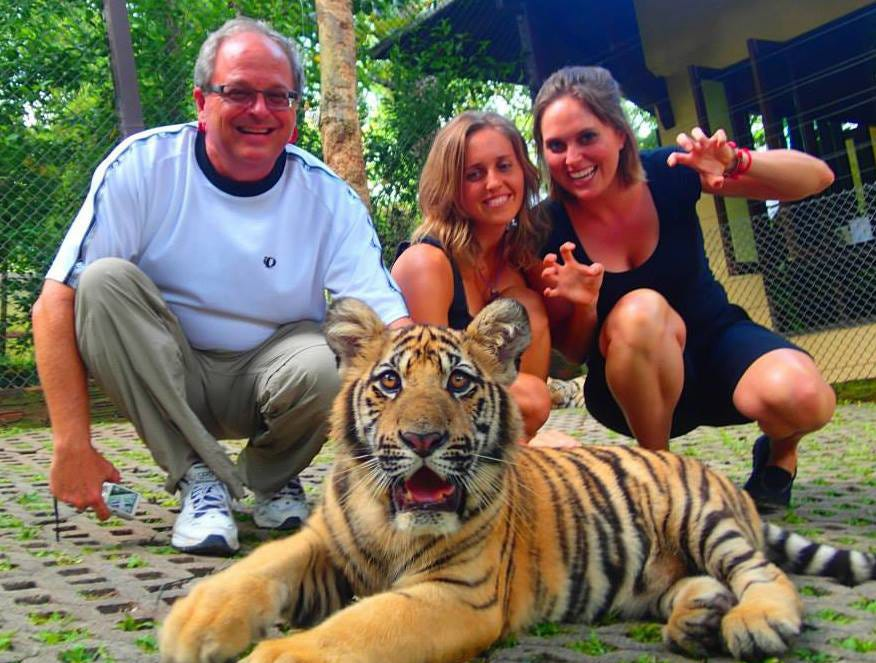 Craig, Amanda, and Heather Woodward with a tiger in Thailand.