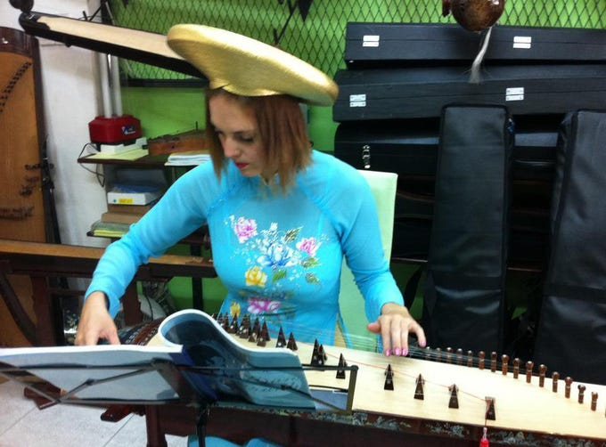 Heather learning to play the Dan Tranh in Ho Chi Minh City, Vietnam. Woodward, daughter of Marco Islander Craig Woodward, has lived all over Asia and traveled all over the world.