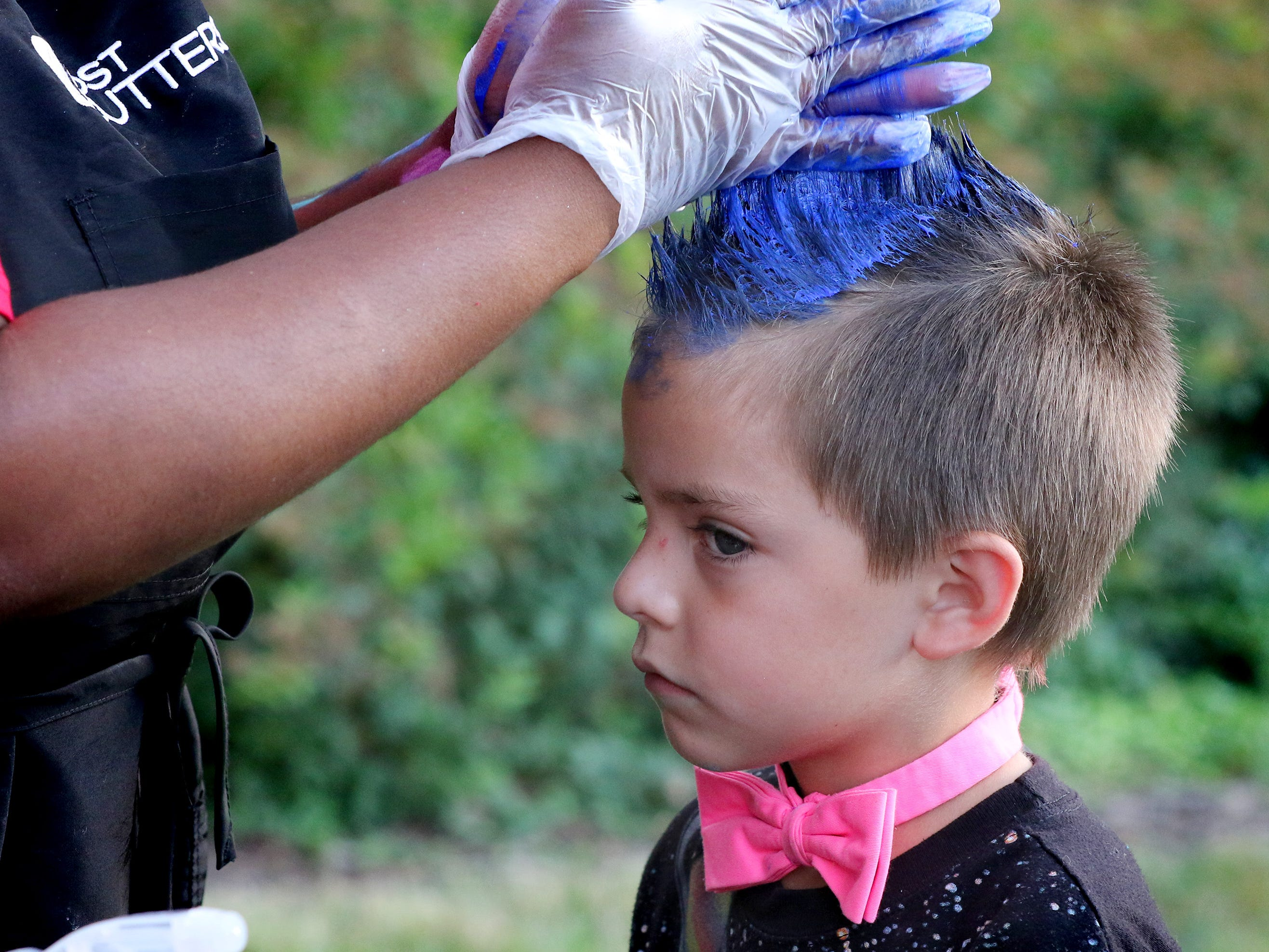 Marcus Hansen, 6, receved a blue mowhawk at the Cost Cutters booth  during Waukesha's National Night Out at Frame Park on Aug. 1.