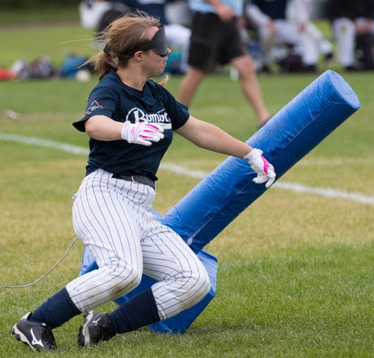 The Long Island Bombers' Megan Fink scores a run after hitting first base during their game against the New Jersey Titans.  When the ball is hit, batters run to either first or third base, which resemble padded football tackling dummies.