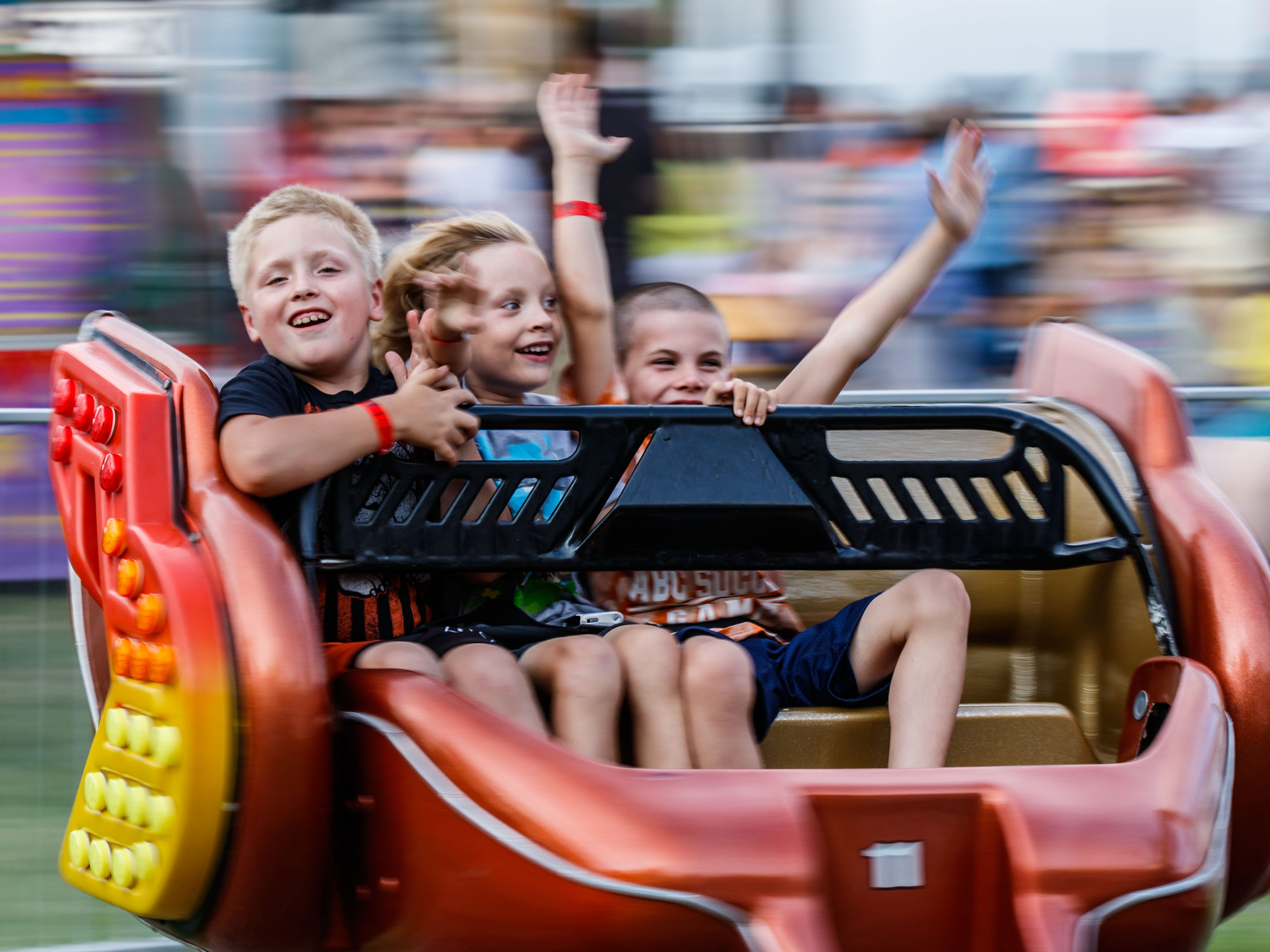 Eli Wilhelme, 7, Jackson Loomis, 6, and Boden Gartman, 8, all of Cedarburg, spin round on a carnival ride at the Ozaukee County Fair in Cedarburg on Wednesday, August 1, 2018.