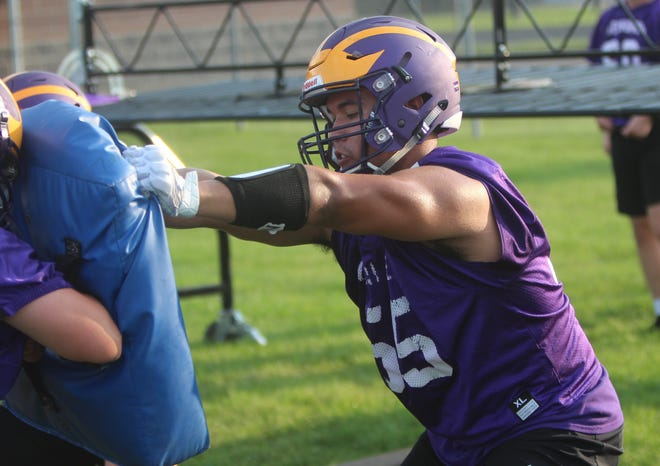 New Berlin Eisenhower senior Mark Shields engages with a blocker during practice on August 1.