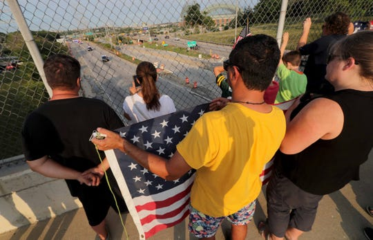 A man holds an American flag as the funeral procession for fallen Milwaukee Police Officer Michael J. Michalski travels along I-94 west near Miller Park.