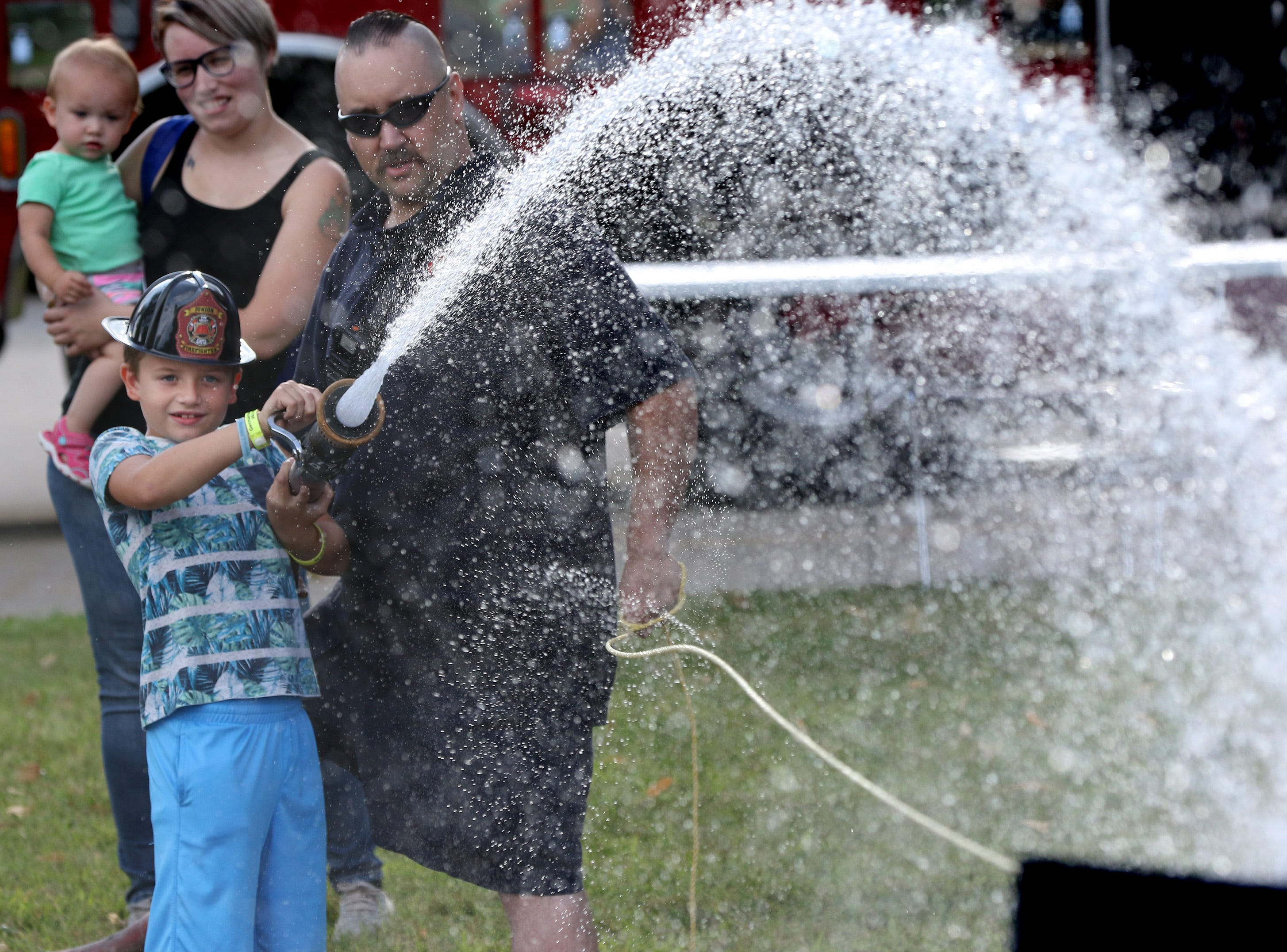 Mason Baier, 8, tries a fire hose with Firefighter/Paramedic Brian Moe during Brookfield's National Night Out at the Brookfield Fire Department Station 1 on Aug. 1.