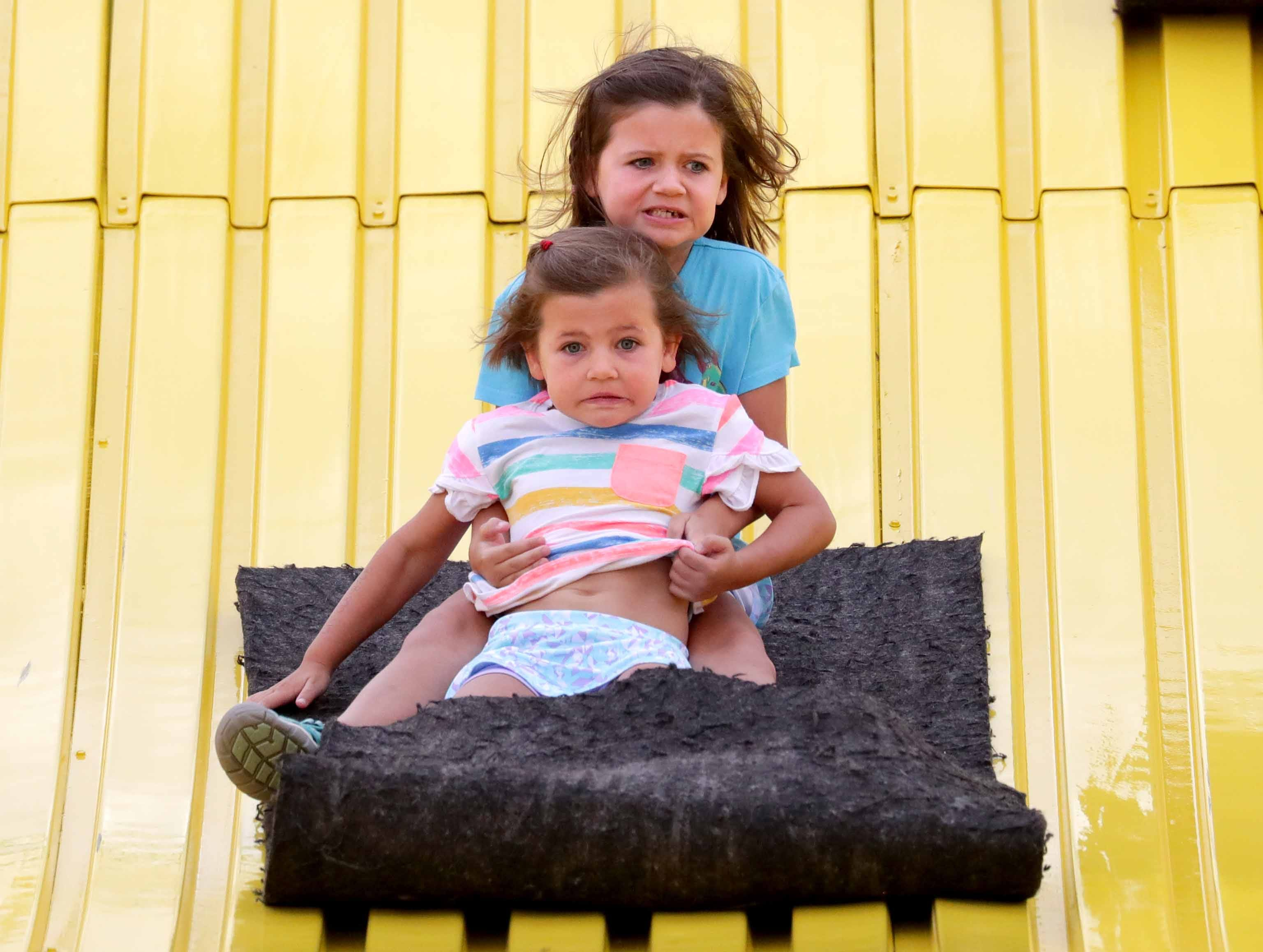 Five-year-old Eleanor Baltz (front) and her 7-year-old sister Evelyn, both from Nashville, Tenn., slide down the  Giant Slide at the Wisconsin State Fair. It's the 50th anniversary of the State Fair's Giant Slide. The girls were with their mother, Sarah Baltz.