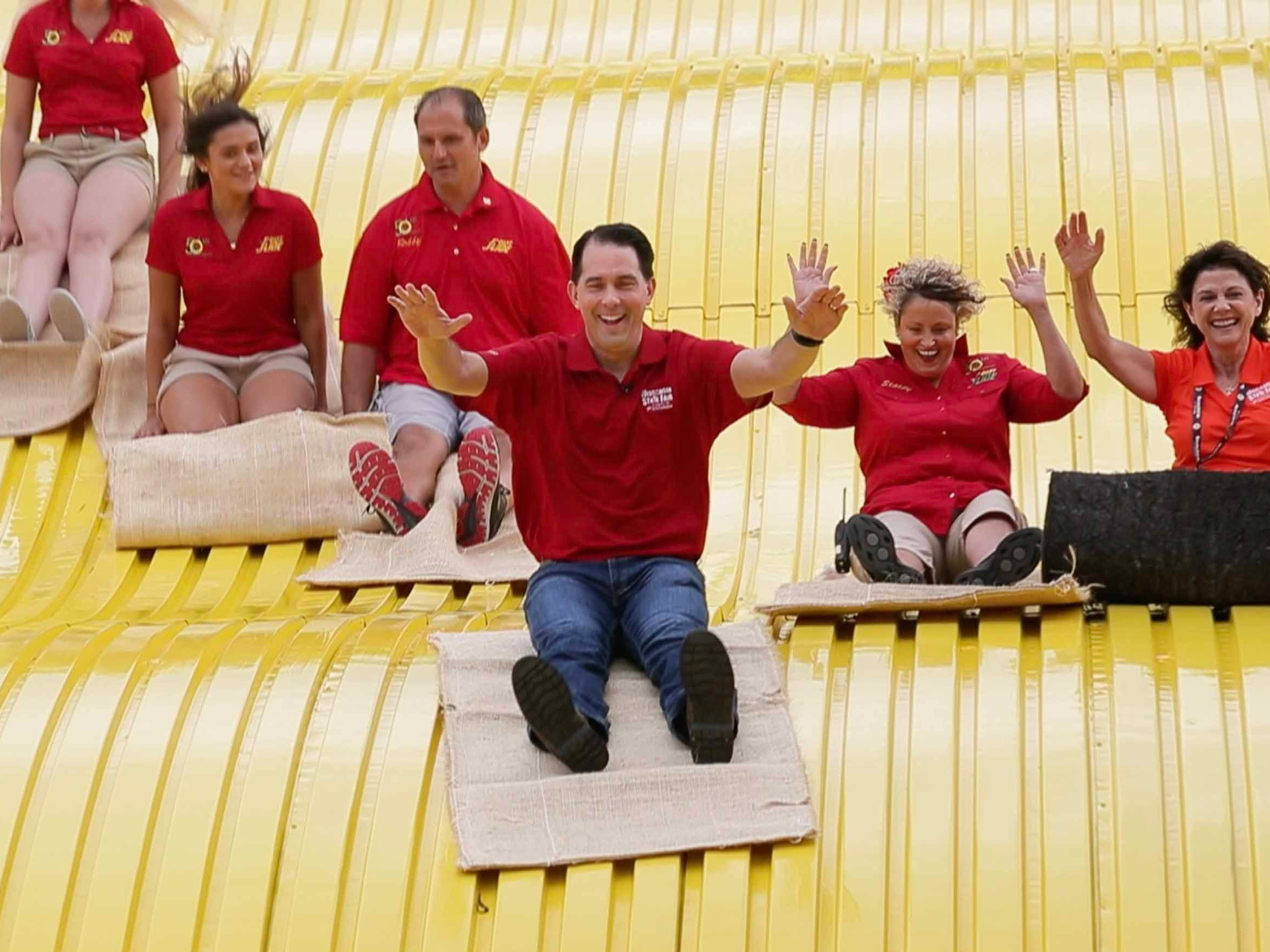 Gov. Scott Walker slides down the Giant Slide, marking the opening of the 167th Wisconsin State Fair and the 50th anniversary of the State Fair's Giant Slide at State Fair Park in West Allis on Thursday, Aug. 2, 2018. He was joined by operators of the slide, from left, Isabella Barona; her sister, Anibella Barona; their father, Robby Barona; and their mother, Stacey Barona. At right is state Sen. Leah Vukmir.