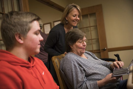 Erin Jakupciak and son Noah looked though a photo album with her mother, Nancy Kreibich, at a memory care facility in La Crosse.