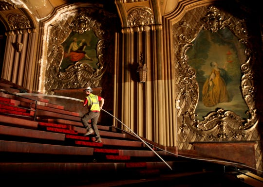 A worker carries a conduit up the balcony stairs at the Warner Grand Theatre, which is being transformed into the Milwaukee Symphony's new concert hall.