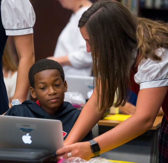 Trinity ambassador Emma Beth Teel helps Alchico Grant log in during sixth grade computer orientation class Thursday, Aug. 2, 2018, at Trinity Presbyterian in Montgomery, Ala. Grant will attend his fourth year at Trinity on a scholarship from the Alabama Accountability Act.
