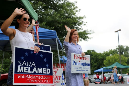 House District 61 candidate Rebecca Purington, right, and volunteer Terri Ward wave at voters at Brenthaven Cumberland Presbyterian Church on Aug. 2, 2018.