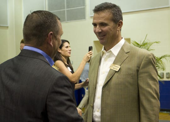 Urban Meyer mingles with FGCU baseball coach Dave Tollett at the Night at the Nest fundraising dinner in 2011at Alico Arena.