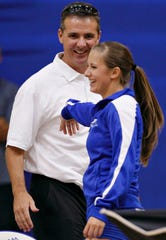 Former University of Florida head football coach Urban Meyer teases his daughter, Gigi Meyer, in between sets during the Florida Gulf Coast University volleyball match against the University of South Florida in 2011 at Alico Arena in Fort Myers.