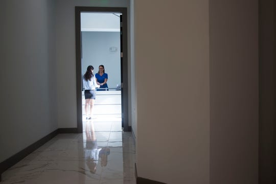 Michelle Castillo, marketing manager, from left, and Amanda Naylor, front desk administrator, review paperwork together before patients are seen on Wednesday, August 1, 2018. Engle Dentistry recently opened its third location off of U.S. 41. The new building located in Naples is distinctive for its sleek and modern design.