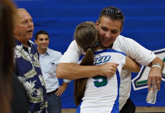 Former University of Florida head football coach Urban Meyer hugs his daughter, Gigi Meyer, after the Florida Gulf Coast University volleyball match against the University of South Florida in 2011 in Fort Myers.