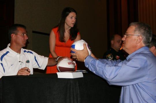 Florida Gators head coach Urban Meyer signs a football for fan Carey Soud, 52, of LaBelle, during the Southwest Florida Gator Club event in 2009 at the Hyatt Regency Hotel in Bonita Springs.