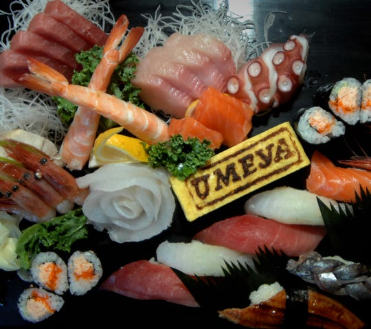 Umeya, Japanese sushi restaurant in Cresskill.  Owners, Masako, left, and Kenji are husband and wife.  Detail:  a large platter of sushi, sashimi, and omakase.