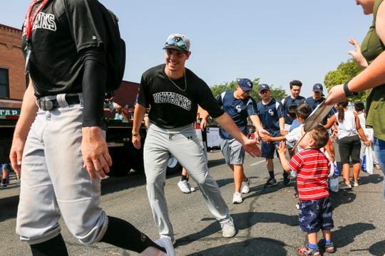 Colton Nighthawks and Connecticut Bombers players exchange high-fives with fans Thursday during the Connie Mack World Series Parade on Main Street in downtown Farmington.