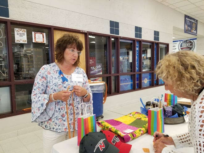 Patti Clark-Stojke explains how a silent auction works Wednesday, Aug. 1, 2018, during the Wisconsin Public Education Network's Summer Summit at Appleton North High School. The Network raised $6,000.