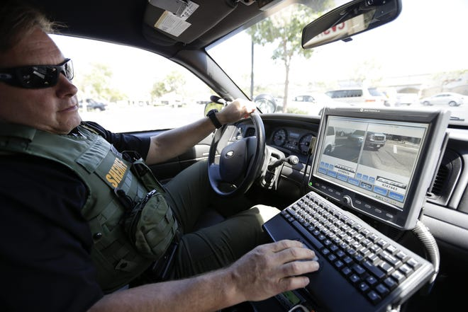 In this 2014 file photo a San Diego County sheriff's deputy checks a license plate database. AP