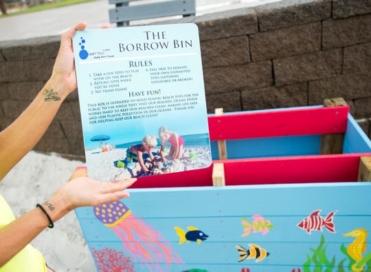 Jennifer Deubler, Ocean Hour project manager, holds a sign Thursday before placing it on a toy borrow bin at Casino Beach in Pensacola Beach.