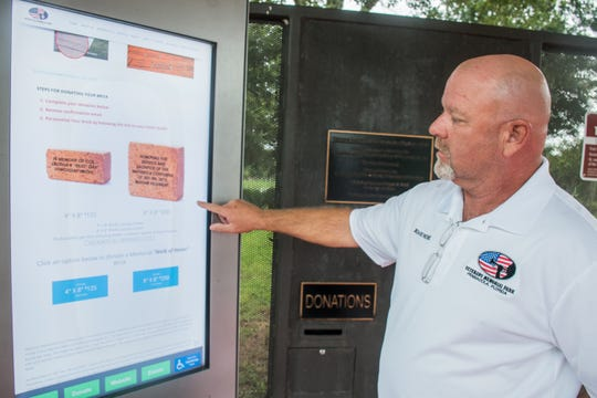 Richard Penrose, a member of the Veterans Memorial Park board, demonstrates how to purchase a commemorative brick at the park's electronic kiosk