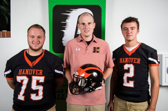 Hanover football head coach Brandon Bishop poses for a photo with players Hunter Laugerman, left, and Jeff Jacoby during YAIAA football media day in Hanover on Thursday, August 2, 2018.