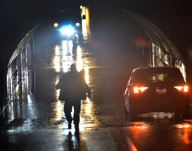 A Chambersburg policeman walks down to a flooded area under a railroad overpass at Woodstock Road where some motorists became stranded after a flash flood in Chambersburg. Rain in the area became steady after 8pm Wednesday, August 1, 2018.