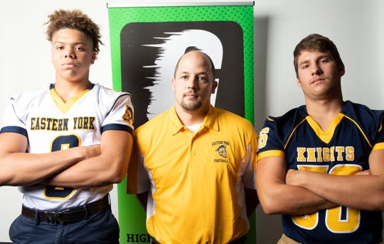 From left, Eastern York's Demonte Martin, head coach Joshua Campbell and Drake Brown pose for a photo during YAIAA football media day in Hanover on Thursday, August 2, 2018.